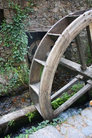 Old watermill with a wooden wheel and stone walls Stock Photo