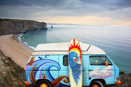vw: A blue van with a surf board at the beach Stock Photo