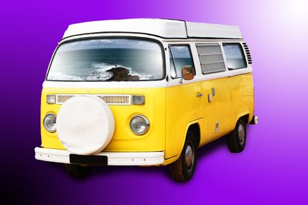 A retro yellow van with the ocean reflex on the windows