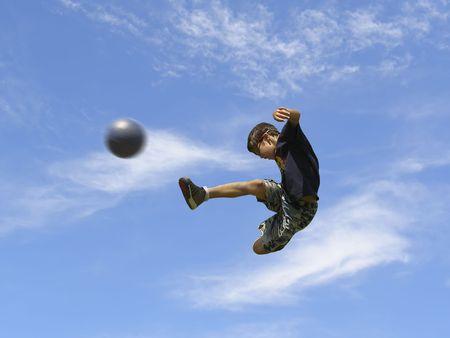 oefenen: Boy voet bal spelen tegen de hemel Stockfoto