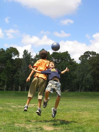 Two boys playing soccer in a gree grass field with blue sky above