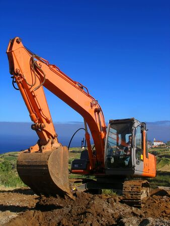 Bulldozer digging a whole with the blue sky as background     Stock Photo