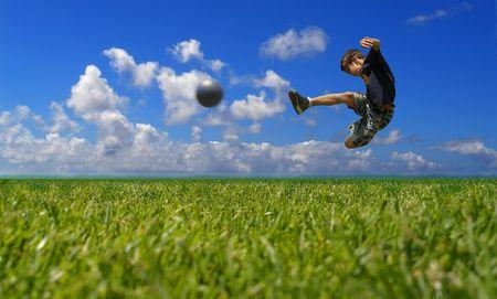 coup de pied: Gar�on joue de football contre le ciel Banque d'images
