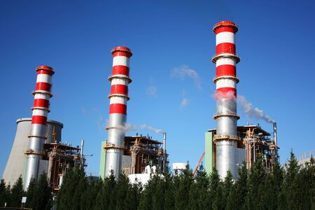 steam turbine: Power plant chimneys producing white smoke against a blue sky