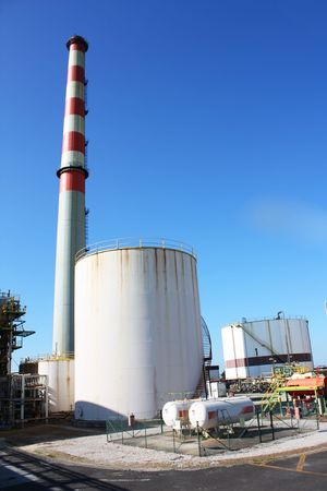 Lots of industrial pipes, a chimney and large reservoirs photo
