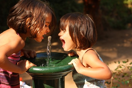 Two little girls smiling and playing outdoors. Drinking water from a water fountain