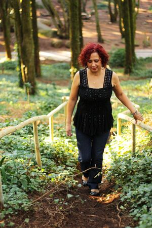 Red hair woman standing outdoors in a beautiful green forest Stock Photo - 8520415