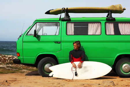 Surfer preparing to go surfing with his green vintage van