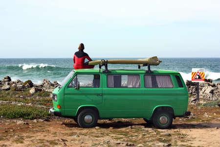 Surfer watching the ocean on top of  his green vintage van