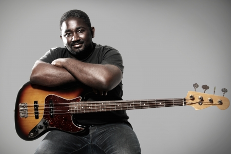 young musician: an american african bass player on white background