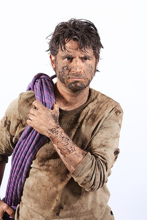 A man covered in mud with a rope, trying to survive Stock Photo - 16640841