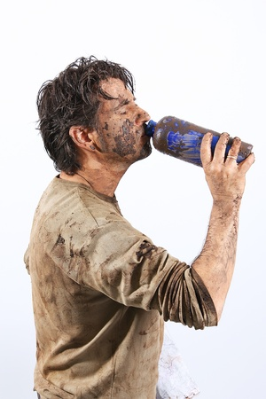 A man covered in mud trying to survive photo