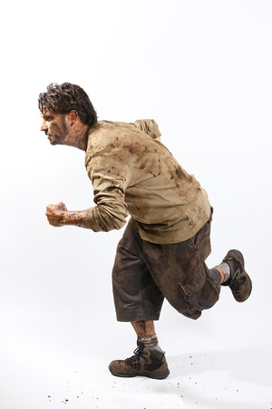 A man covered in mud running, trying to survive photo