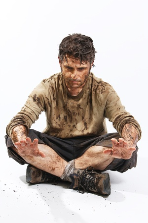 A man covered in mud sitting on the floor, trying to survive photo