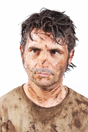 A man covered in mud trying to survive