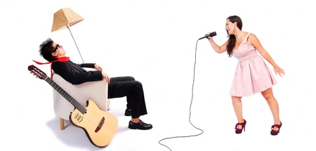 blown away: A female singer and a male guitarrist in action in white background  The musician is blown away by the powerful voice of the singer