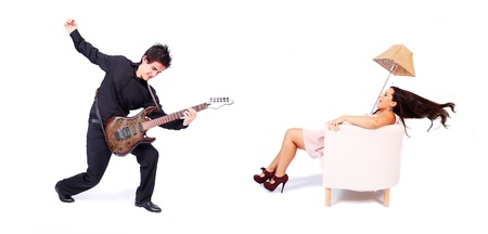 A female singer and a male guitarrist in action in white background  The singer is blown away by the powerful sound of the guitar