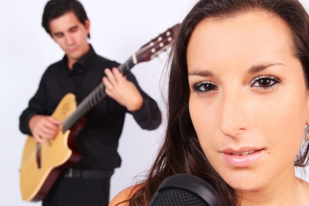 A female singer and a male guitarrist in action in white background photo