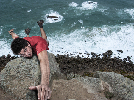 climbing: aventura del hombre de escalada en roca cuelga de un acantilado