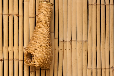lamphun: Bamboo eel trap norther Thai style hanging on bamboo wall Stock Photo