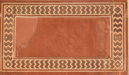 inlaid: Wall of Taj Mahal, India with intricate designs and patterns in red sand stone with inlaid marble