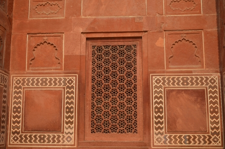 burried: Wall of Taj Mahal, India, with intricate designs and patterns in red sand stone with inlaid marble