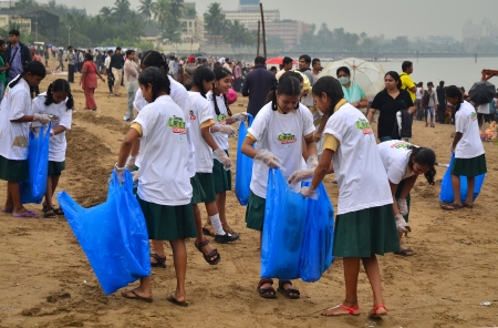 immersion: Mumbai, India - September 2013 - Volunteers students helping to clean up the beach during the rain after the immersion of Hindu God Ganesha