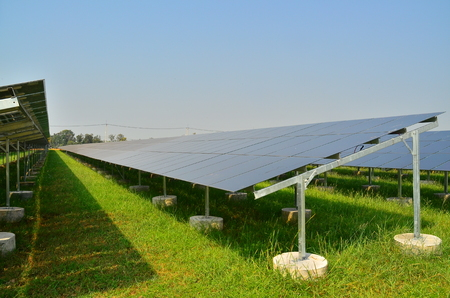harnessing: Solar cell panels in the field during daytime against strong sunlight and clear blue sky to generate electricity Stock Photo