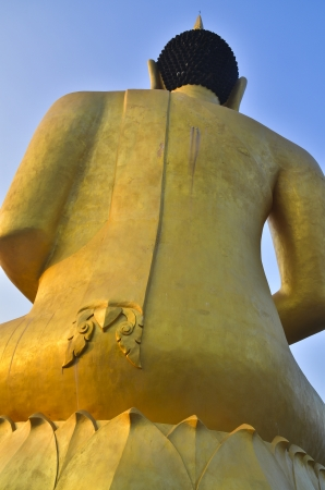 statute: Back view of big Buddha statute in gold color sitting against blue sky