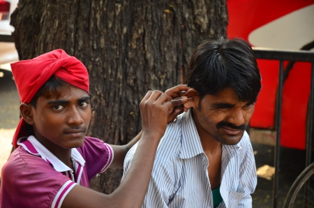Mumbai, India - February 2013 -  man picking earwax for his customer