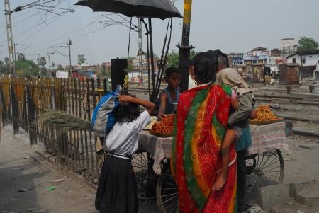 ni�os vistiendose: Bihar, India - 05 de abril 2012 a una madre con un vestido sari rojo que lleva a su hijo de comprar dulces de puesto de carretera Editorial