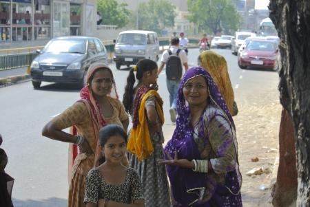 ni�os vistiendose: Ahmedabad, India - 28 de Setiembre de 2011 La madre de Gujarat con sus hijas est�n esperando bajo la sombra de los �rboles de un autob�s