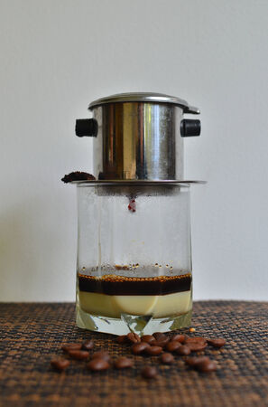 condensed: Vietnamese Coffee dripping on clear glass with condensed milk