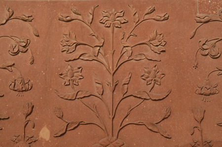 Wall of Taj Mahal, India with intricate designs and patterns in red sand stone with inlaid marble