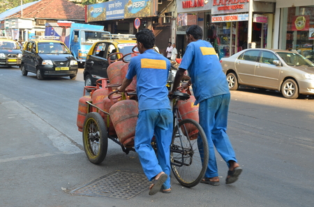 Mumbai, India - December 2013 - Workers delivering LPG gas cylinders on the busy street