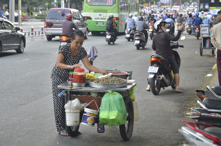 ���push cart���: Ho Chi Minh City, Vietnam - October 2013 - Street vendor selling snack from her push cart on the busy street Editorial