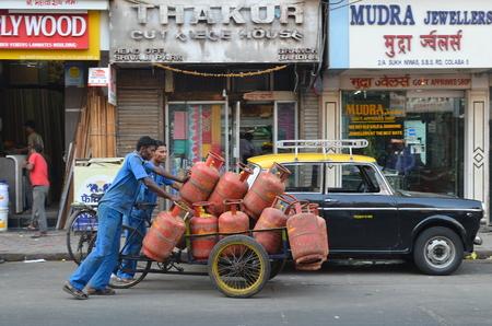 l p g: Mumbai, India - diciembre de 2013 - Los trabajadores que entregan los cilindros de gas LPG en la concurrida calle