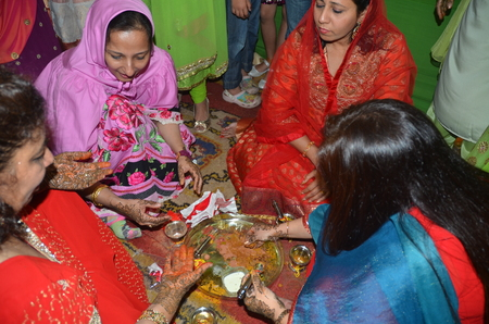 bridegrooms: Mumbai, India -  January 2014 - Ladies performing rituals during traditional Indian wedding ceremony