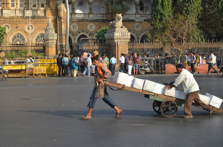 Mumbai, India - January 2014 - Workers pulling goods cart in the middle of street in front of Victoria Terminus