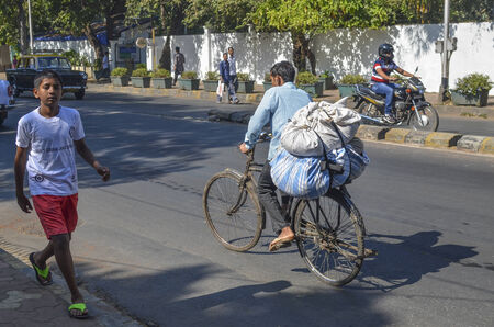 Mumbai, India, January 11, 2014 - Man riding bicycle along the street carrying buldles of clothes for laundry