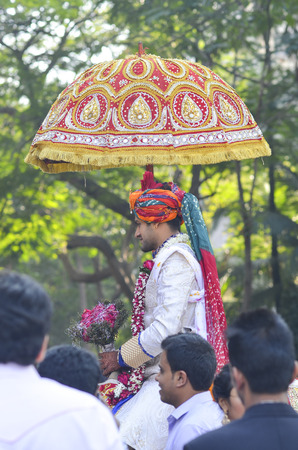 procession: Mumbai, India - bridegrrom in traditional dress riding a horse at wedding ceremony along the street