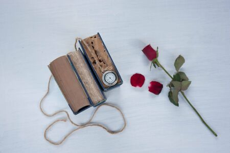 old book rose and locket watch on white background