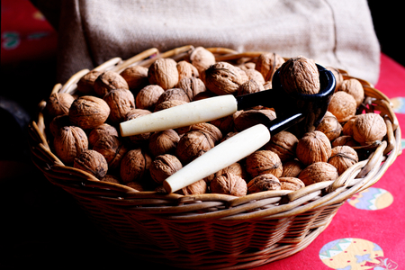Spot focus walnuts(brain) and nut cracker in basket Stock Photo