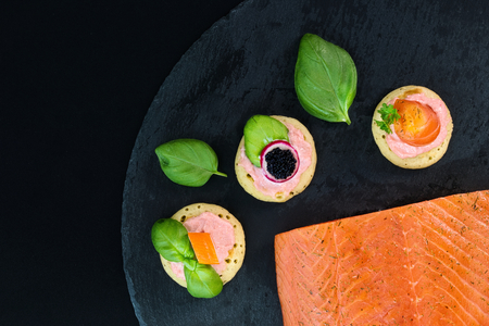 blini: Homemade pancake canapes and piece of smoked salmon on slate stone plate for finger food party