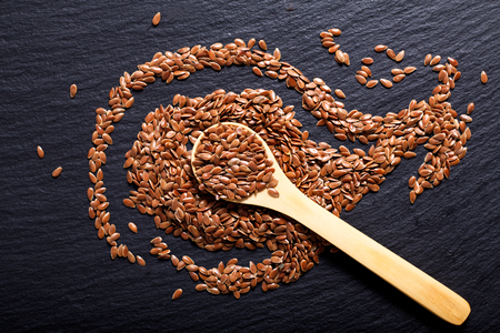 linseed: Organic Flax seeds in wooden spoon on black slate stone plate Stock Photo