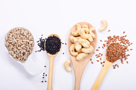 Healthy food concept top view sunflower seeds, cashew nuts, black sesame and flax seeds on white background