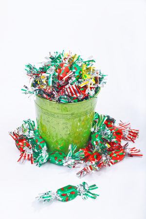 Colorful candy and green bucket on white background