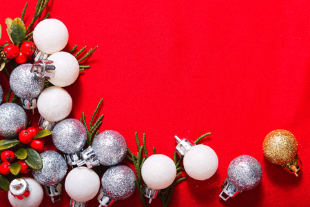 New year or Christmas celebration background glitter balls and leaves decoration on red background