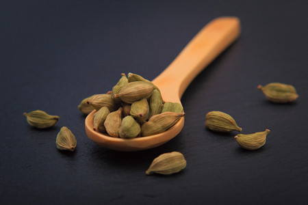 Healthy Food concept Aroma Spice dried Cardamoms in wood spoon on black slate background with copy for text