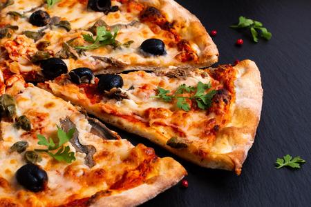 Homemade Napoli Pizza or anchovies pizza on black slate stone Stock Photo